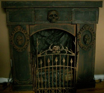 Happy Halloween everyone , Had so much fun making the Grandfather Clock ( thank you all for the compliments ) from cardboard I decided I needed a fireplace to go with it . Same idea as the clock with the mirror frames,plastic web and skulls from Dollar Store , fake fire from a yard sale ($2) and the Spirit cemetery fence from a garage sale ($2) .  Different camera setting to show the web detail . Thanks to Halloween Forum and members for providing a great place to learn an