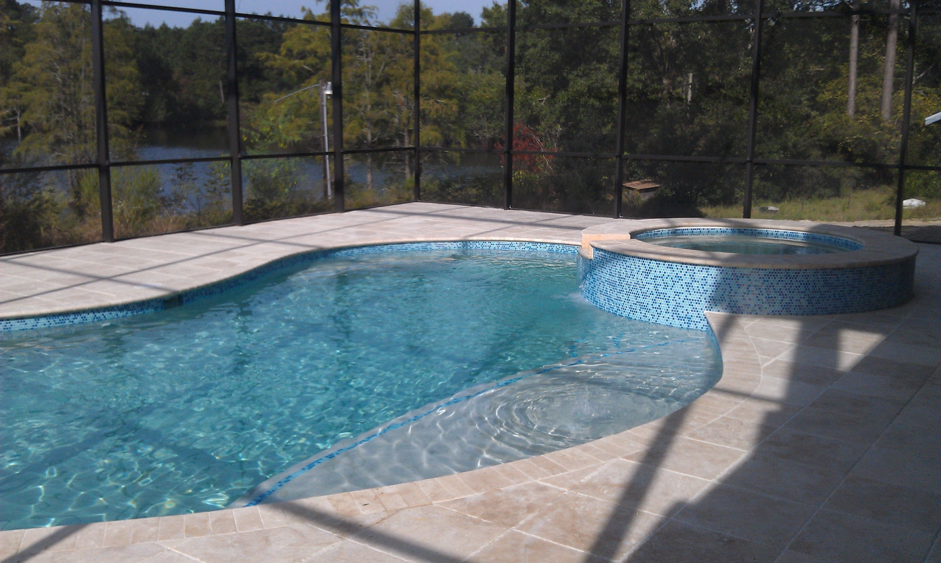 this pool included glass mosaic tile, travertine tile deck