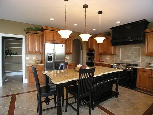 Oak cabinets with black island and stove, tile floors, stainless steel appliances | Trendy ...