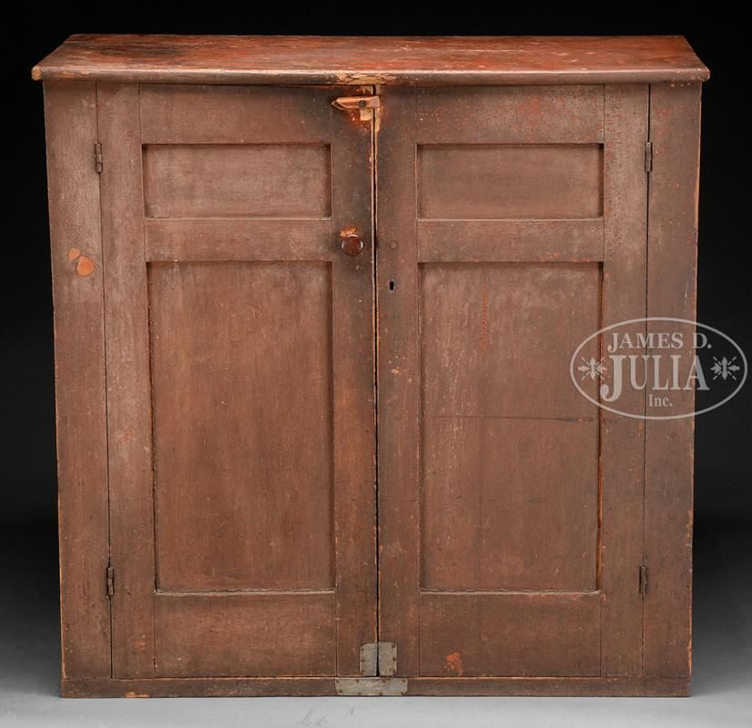 """FINE HUDSON RIVER VALLEY PANTRY CUPBOARD. Circa 1800, New York State. The rectangular pine double door cupboard with single board top in reddish brown paint fitted with a pair of double panel doors opening into an interior fitted with two fixed shelves in primary red paint with traces of old blue. Cupboard retains early, if not original, shaped wooden lock mechanism. SIZE: 42-1/2"""" h x 43"""" w overall x 18-1/2"""" d."""