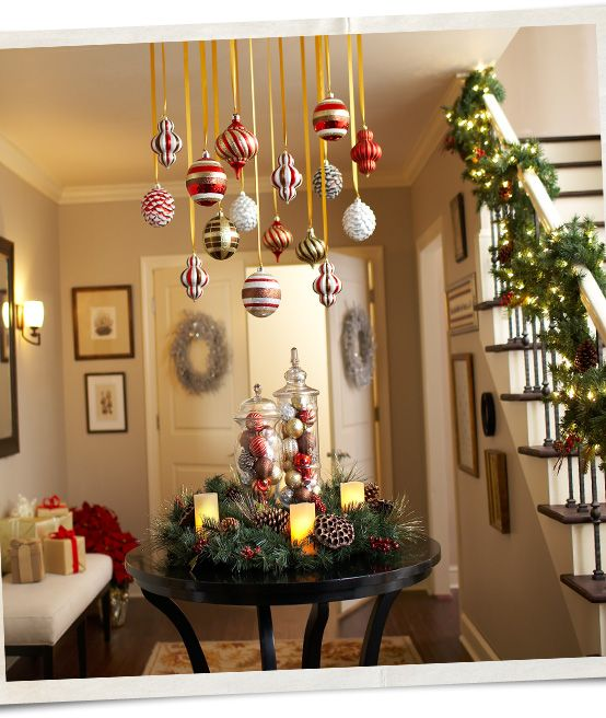 A Festively Decorated Table Sits Under Ornaments Hung From The Ceiling At Vario Christmas Hanging Decorations Christmas Ceiling Decorations Farmhouse Ornaments