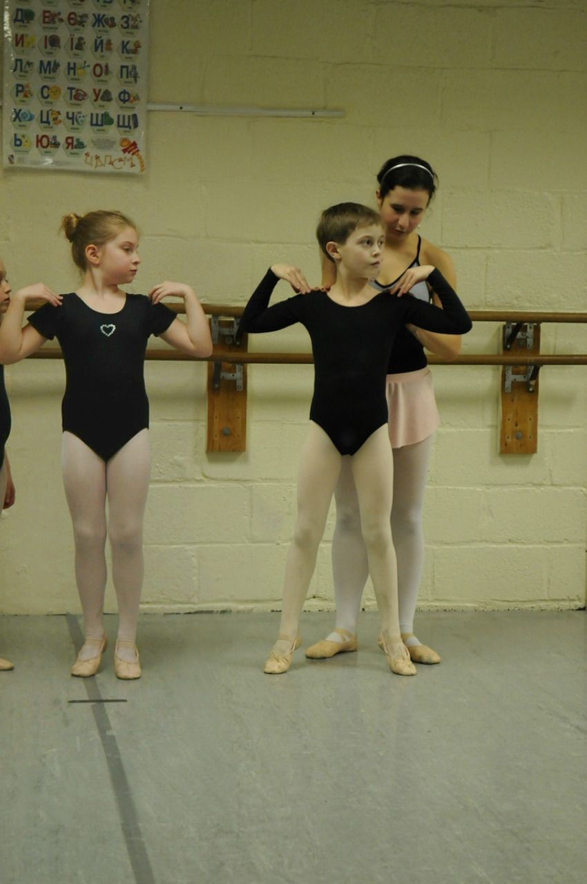 Boy in pink tights, black leotard, and pink ballet shoes