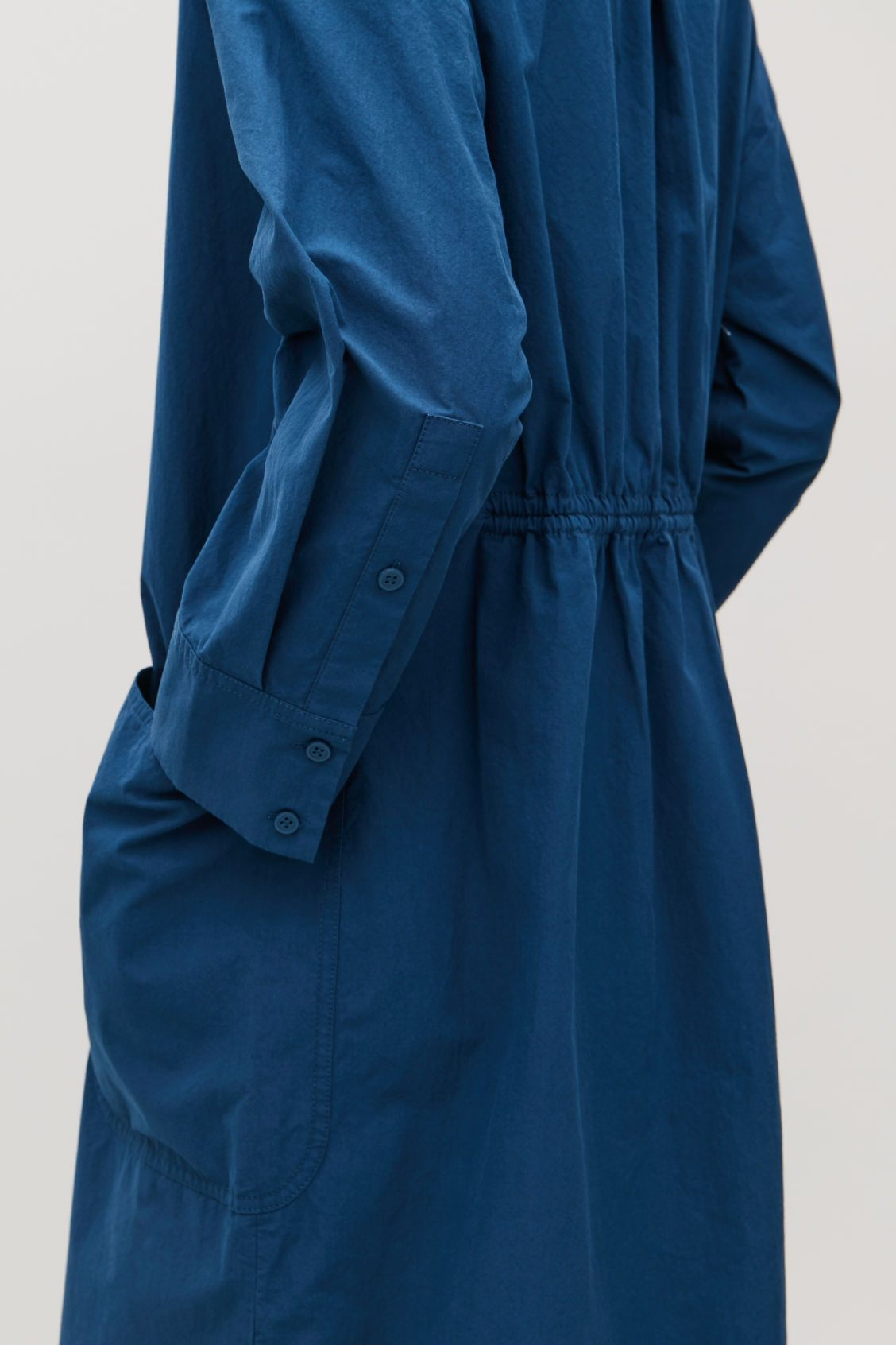 1de5c748f8127 Model side image of Cos long jacket with gathered back in blue | COS ...