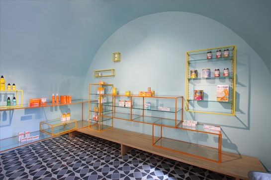 metal-framed shelving in pop colors at De los Austrias Pharmacy by Stone Designs