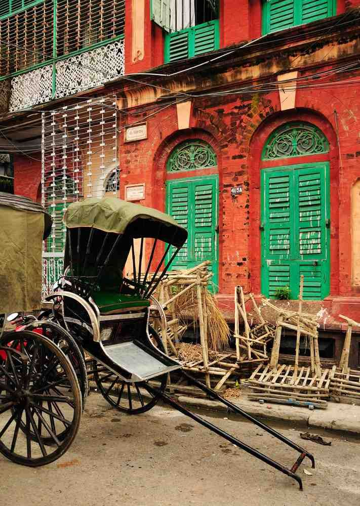 Traditional hand pulled Indian rickshaw parked in front of a old building in Kolkata