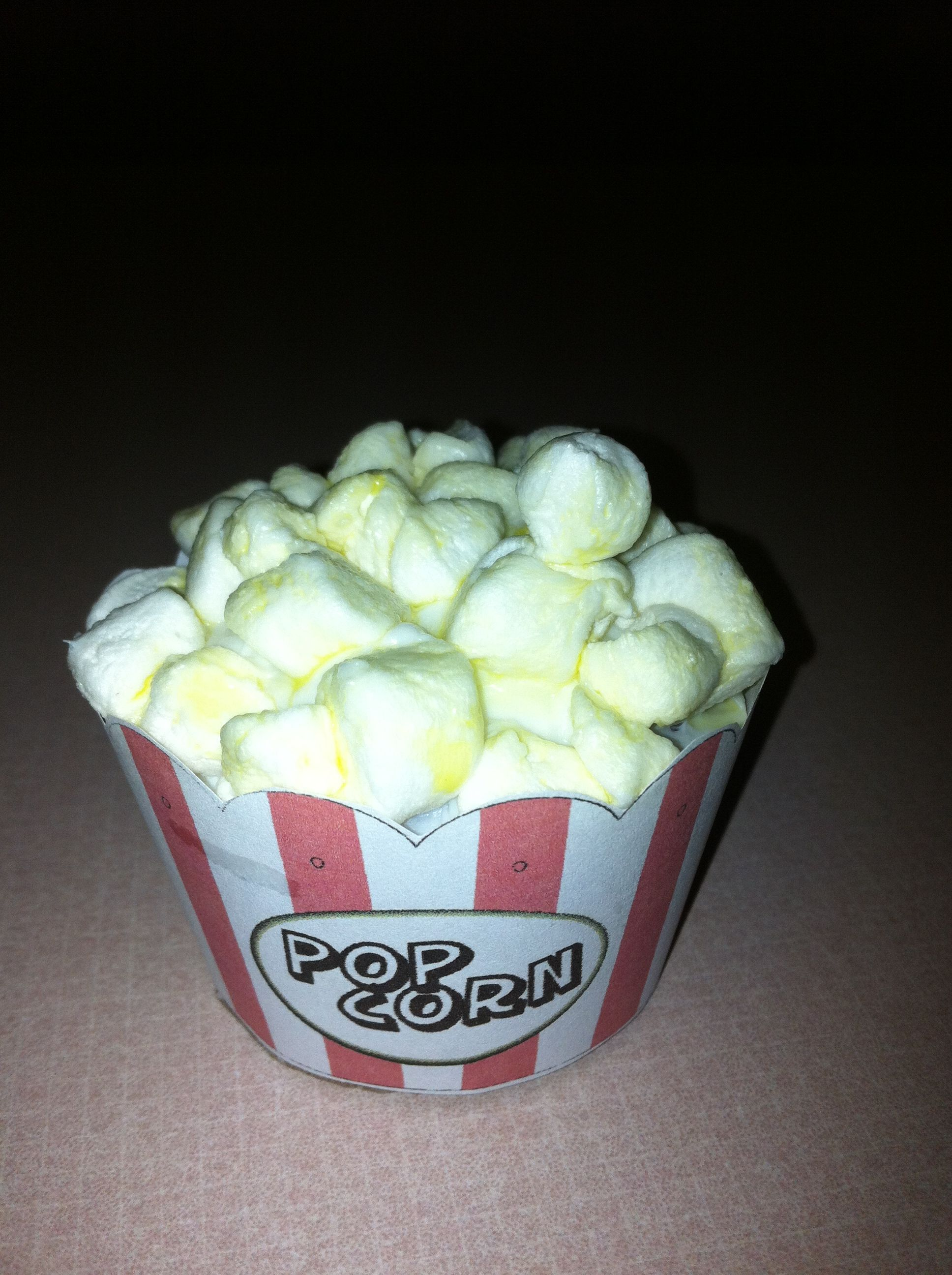 """Great cupcakes for movie night!  """"Butter"""" the marshmallow """"popcorn"""" by brushing it with water tinted with yellow food coloring.  I downloaded and printed the popcorn bucket wrapper."""