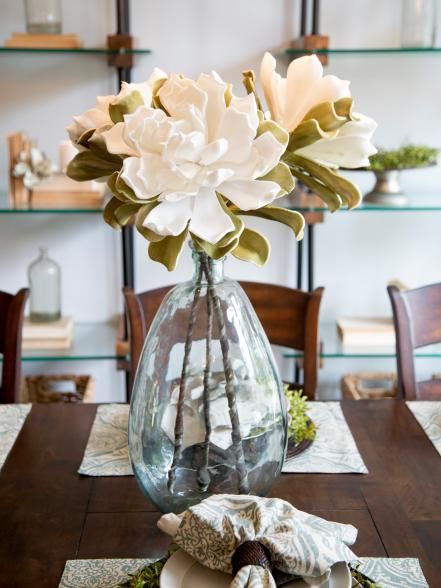 A Large Glass Vase With Elegant White Flowers Serves As Centerpiece For The Table In