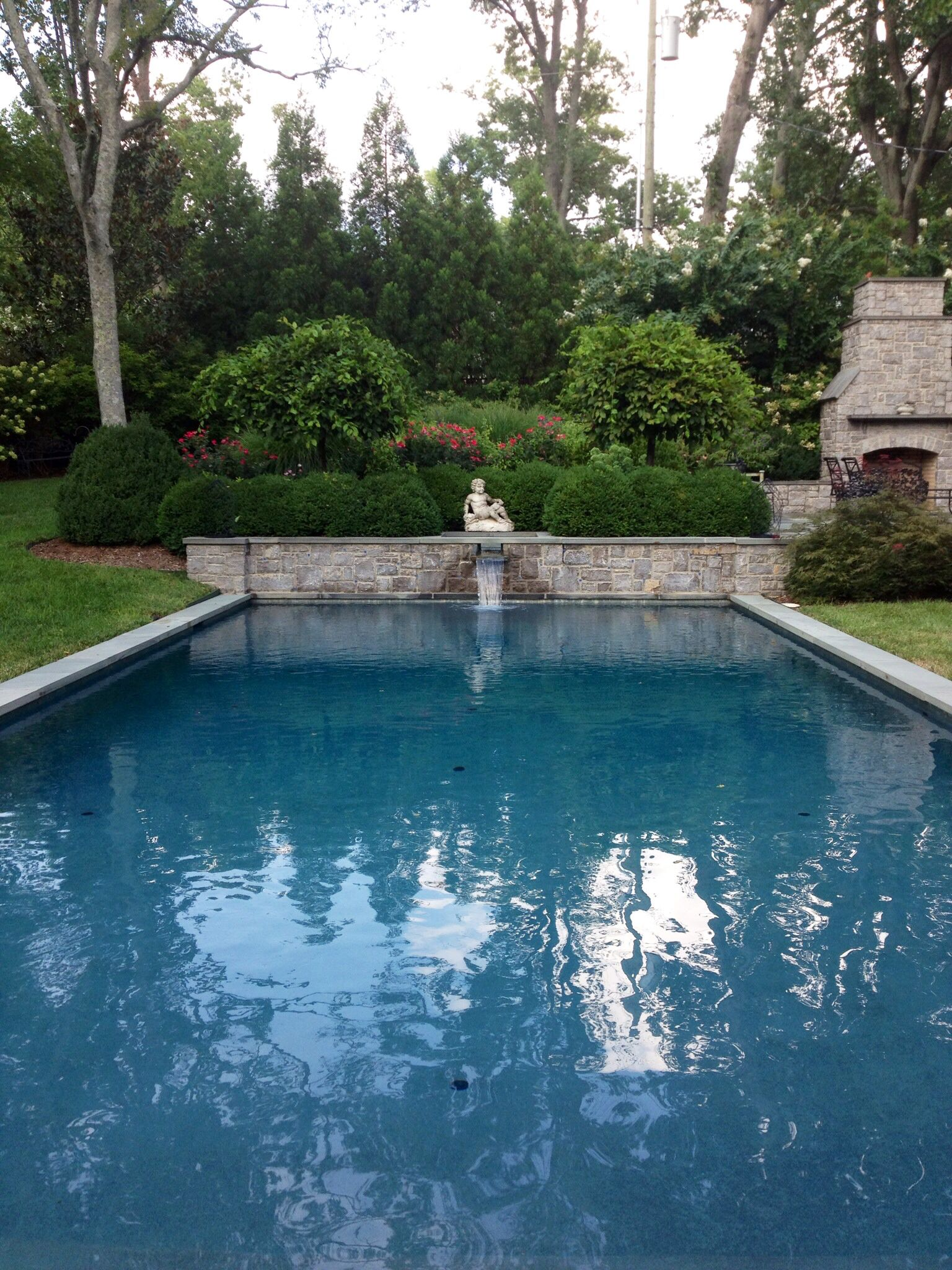 Mediterranean blue pool with stone scupper.