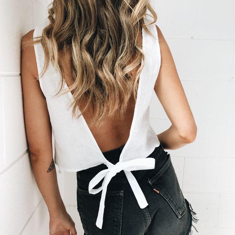 white tie back tank top and vintage black Levi's cutoffs