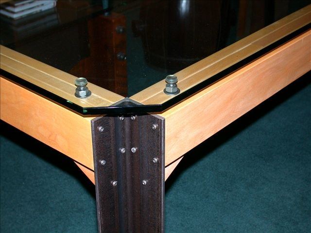 Detail of table with reclaimed industrial i-beams and bolts and new glass top