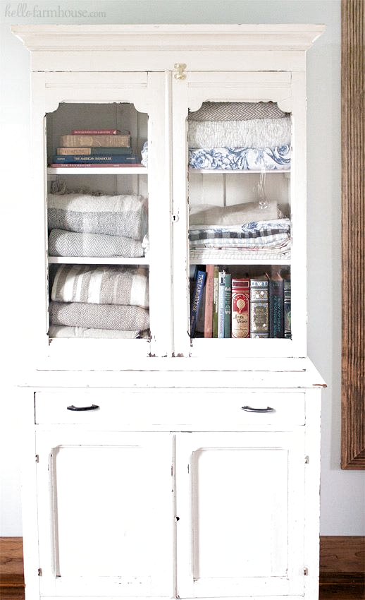 Use an old farmhouse cabinet in the bedroom for extra storage and vintage charm. #farmhouse #farmhousestyle #fixerupper #linencloset #linencabinet #farmhousedecor #homedecor