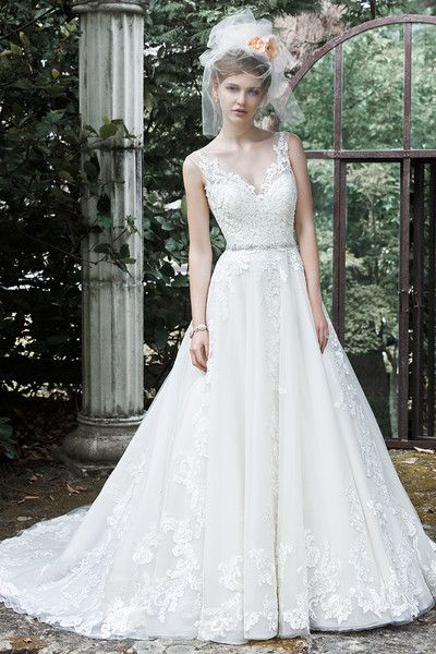 Sybil  This exquisite ball gown wedding dress is complete with floral lace appliqués drifting down a tulle skirt, an elegant illusion V-neckline, and a glittering Swarovski crystal belt. Finished with plunging V-back and crystal buttons over zipper closure.