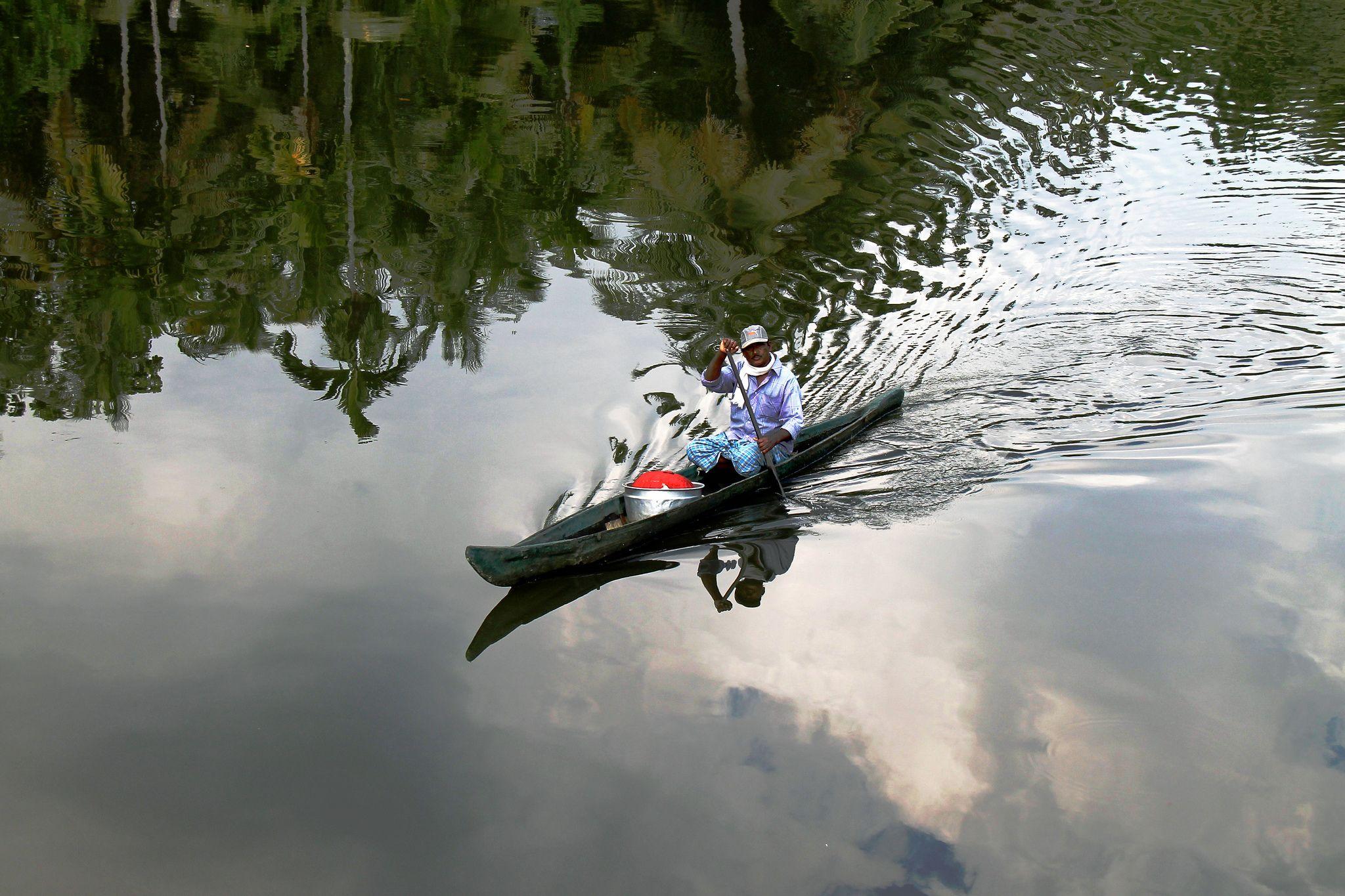 https://flic.kr/p/dYRpWL | Man,boat and reflections.... | boat trip at Vembanad lake, Kerala, India