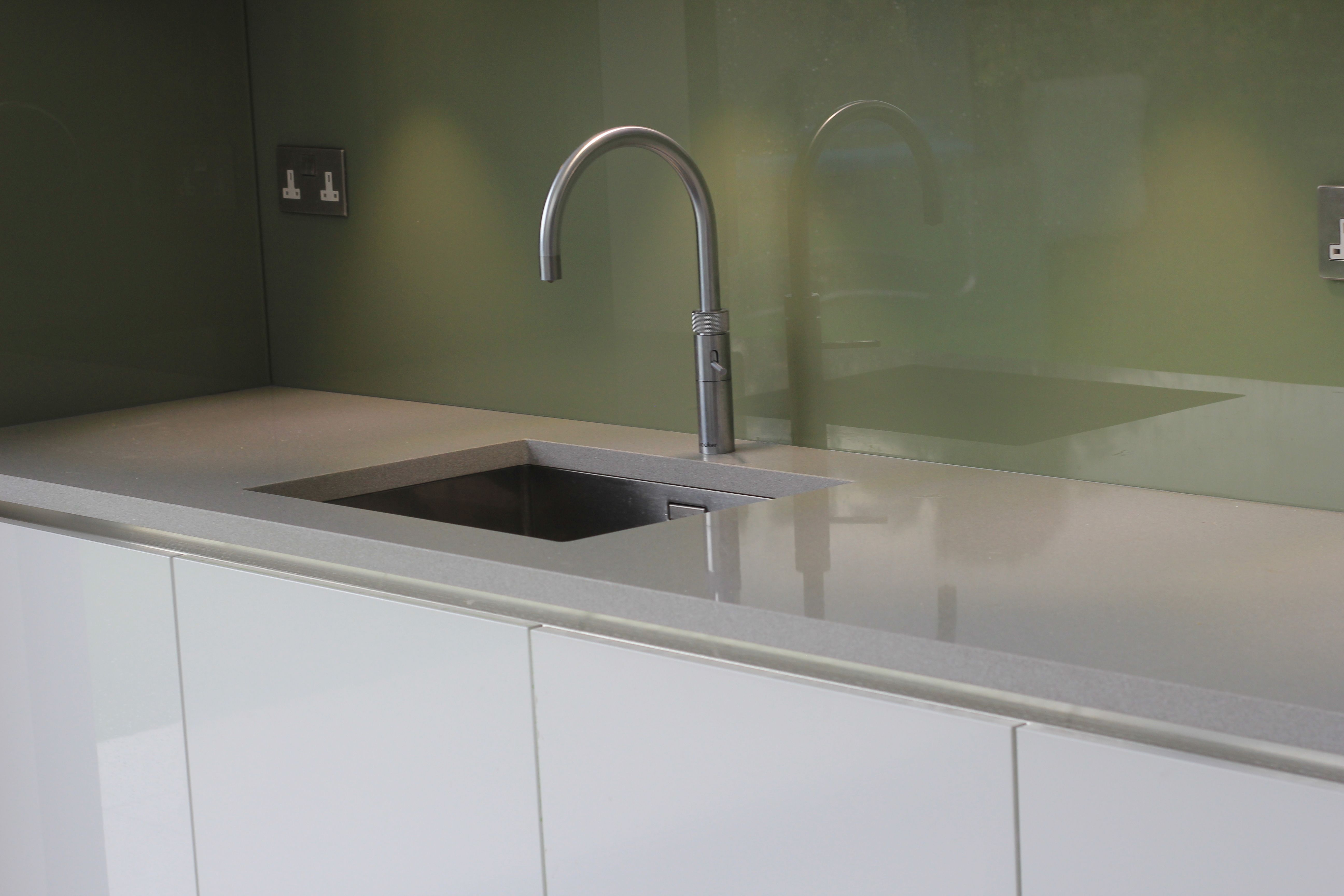 Solid Surface · Silestone Aluminio Nube Grey / Silver Quartz Worktops With  Green Glass Splashback And Undermount Sink.