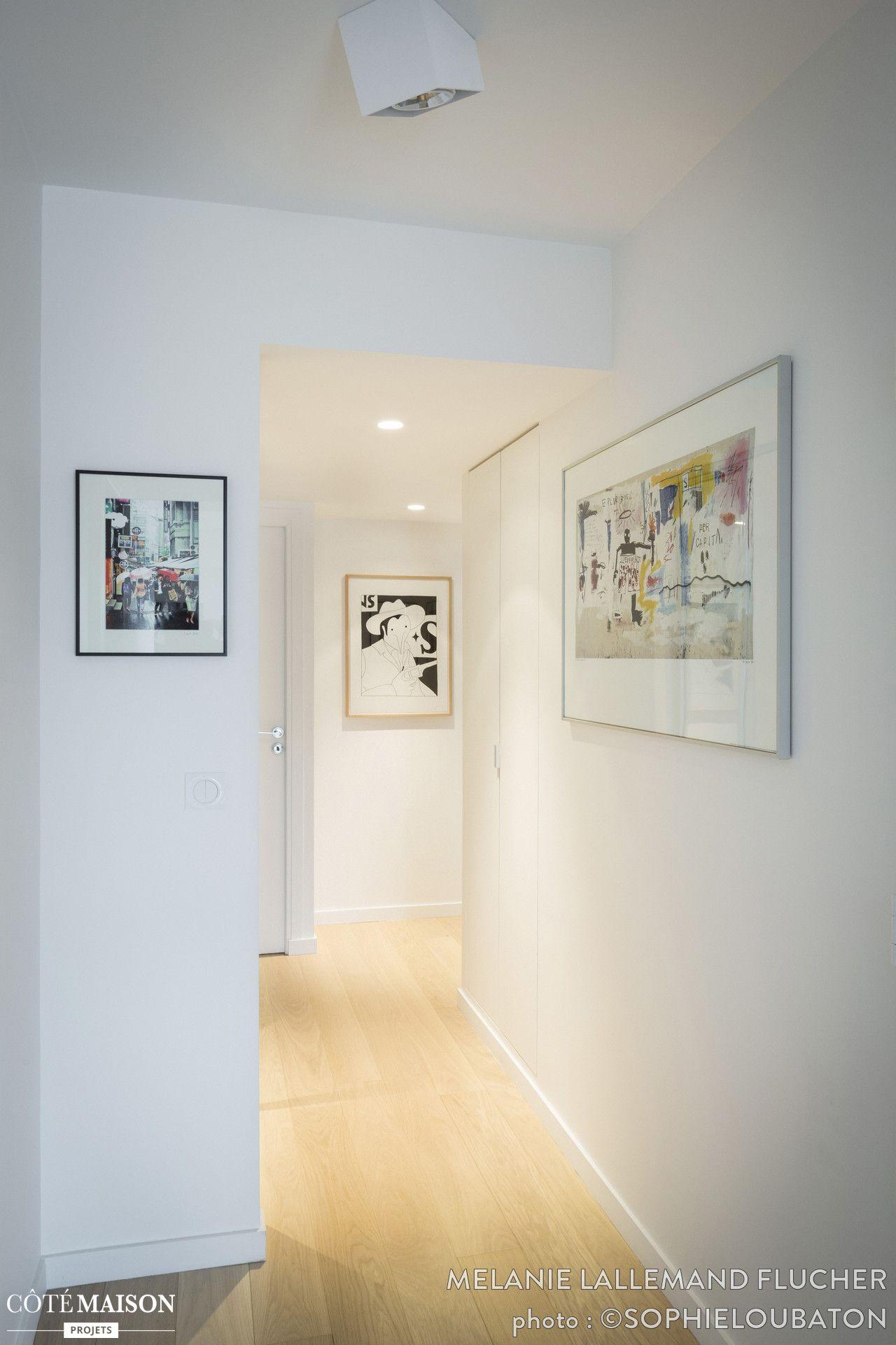 Couloir d\'un blanc immaculé avec parquet en bois clair et cadres ...