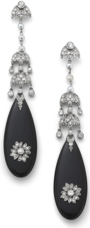 A pair of onyx and diamond ear pendants. Each designed as an onyx drop with applied circular-cut diamond foliate motif suspended from a seed pearl and similarly cut diamond foliate drop and surmount, length 6.5 cm. Via Phillips.