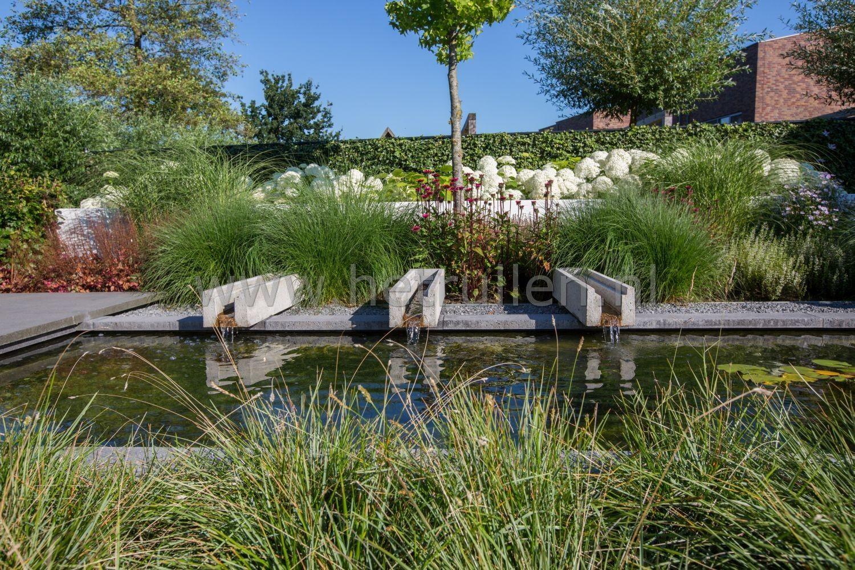 Strakke vijver met vaste planten border en waterspel van beton
