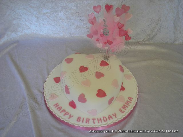 Heart Cake. Heart shaped heart themed celebration cake in white with simple two tone pink sugar hearts. Topped with an all pink feathered and wired explosive topper