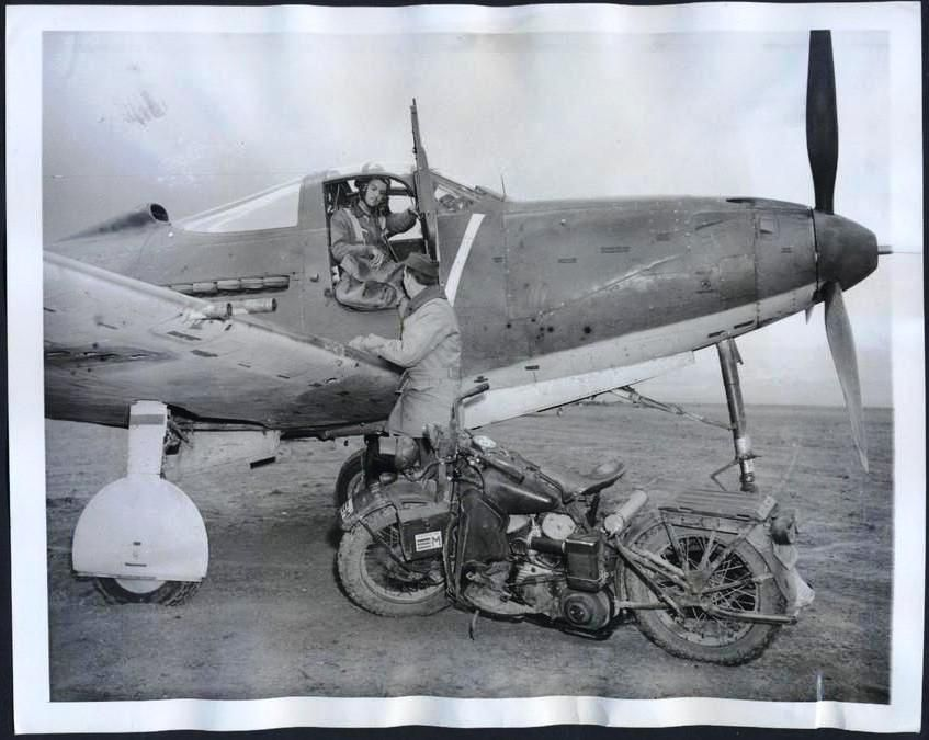 War dispatches being handed off from Harley rider to P-39 driver, 1 of 2. See nearby for back of photo details.
