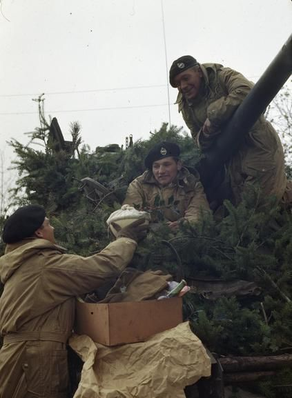 CHRISTMAS WITH THE BRITISH LIBERATION ARMY IN HOLLAND, NOVEMBER 1944.   A tank crew of the 4th Battalion, the Royal Tank Regiment, 4th Armoured Division, unpack a Christmas parcel near Weert in Holland. The crew who are shown with their camouflaged tank looking like a 'travelling Christmas tree' had been together for three years. They had seen action in Libya and Italy before coming to Holland. Left to right: Trooper R Buckley; Trooper J Round; and Sergeant H Kirk.