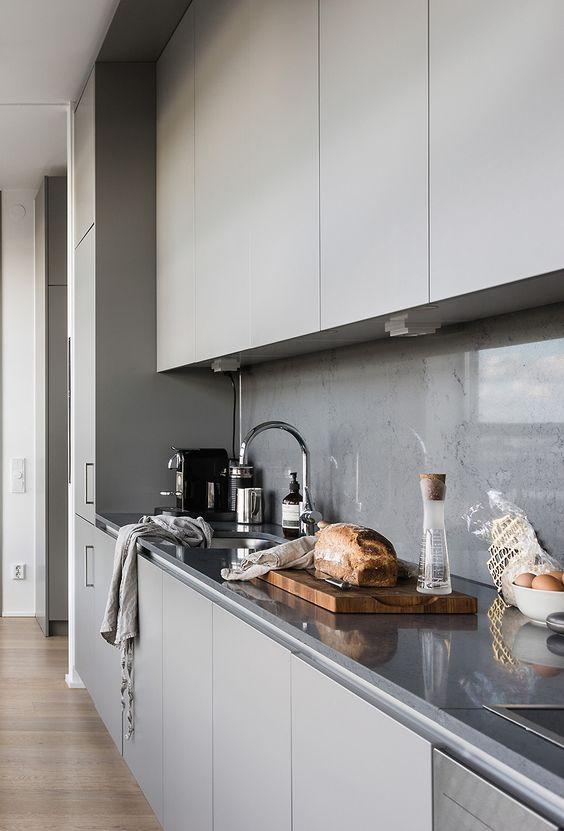 A Minimalist Grey Kitchen With A Concrete Backsplash