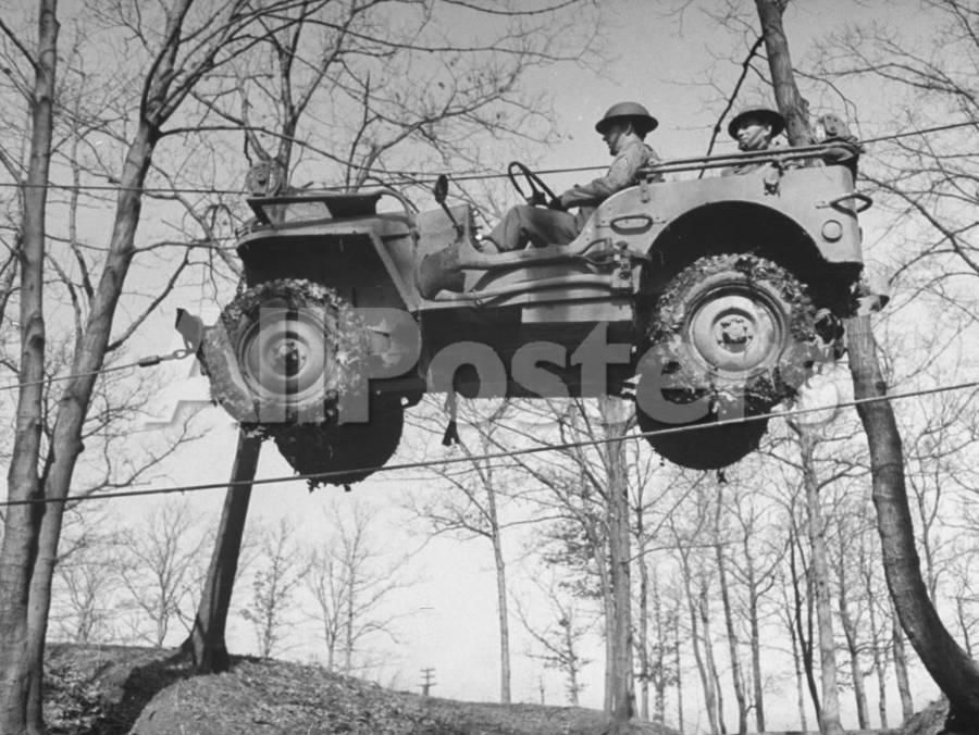 Group Of Us Soldiers Pulling A Jeep Over A Ravine Using Ropes