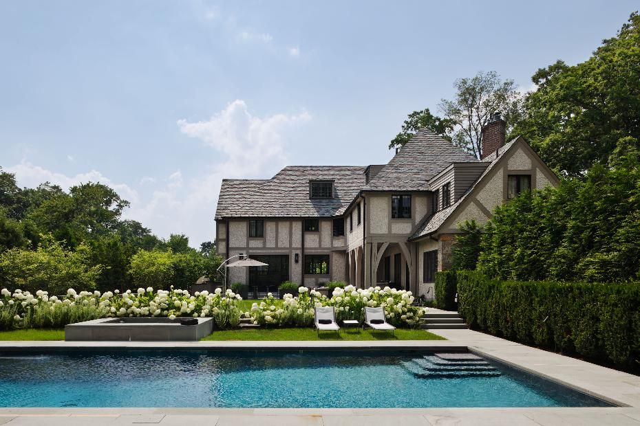 Pristine pool behind a modern Tudor style home.   Tudor ...