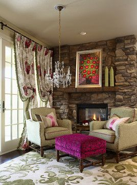 A pop of color was brought into this kitchen sitting area by pairing a fuchsia velvet ottoman with a green leopard print set of arm chairs, a modern floral drapery fabric and original oil artwork above the stone fireplace.