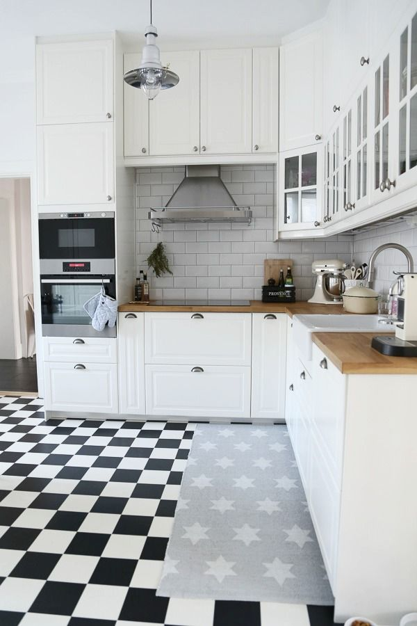 Smaller black & white tiles white cabinets butcher block counter