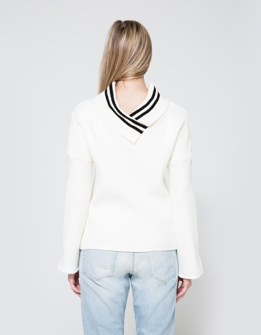 From Frankie, a thick, modern sweater in Ivory. Fold-over collar. V-back. Dual accent stripes at neckline. Dropped shoulder. Long bell sleeves. Half-inch white trim at cuffs and hem. Casual fit.   • Rib knit • 100% cotton • Dry clean • Made in USA