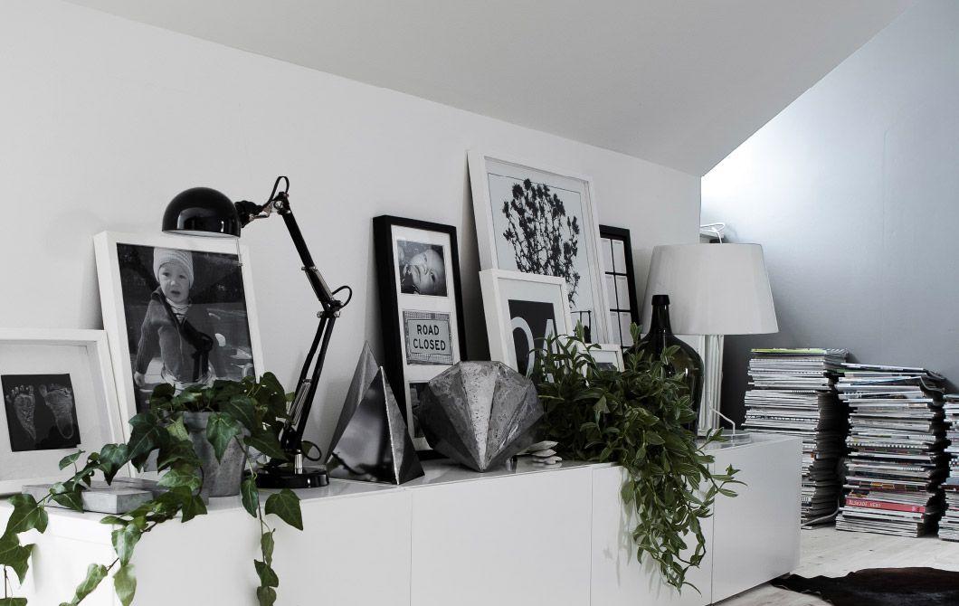 Molduras sobrepostas com imagens, candeeiros e ornamentos compõem uma exposição de prateleira impressionante
