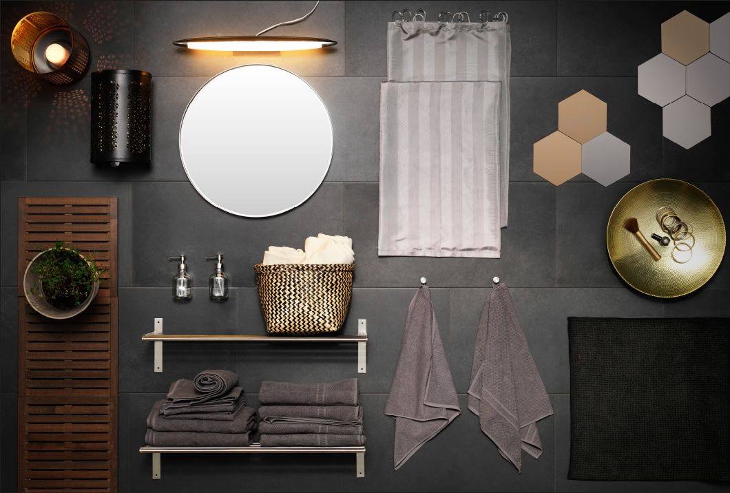 ダークグレーのスレート材をバックに、エスニック調のゴールドとグレー系のバスルームアクセサリー、照明、テキスタイルをコラージュ風にディスプレイ