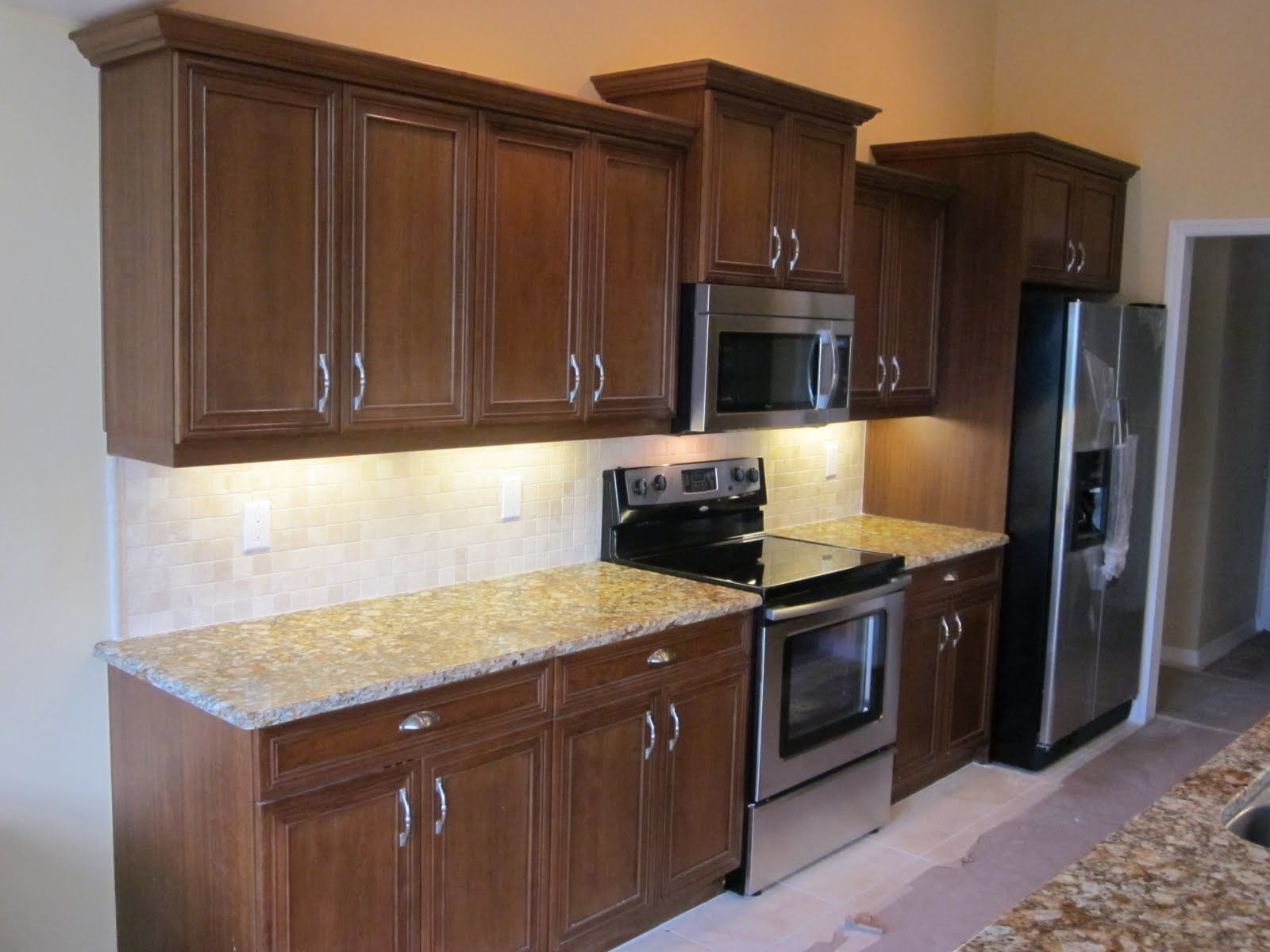 This Transitional Straight Line Kitchen Layout Features Walnut Cabinets U0026  Off White Wall Accents.