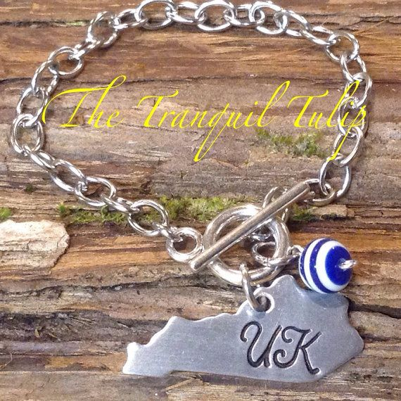 On, on, U of K, we are right for the fight today.... Love those CATS! You too? Then youve come to the right place! The bracelet pictured has an aluminum Kentucky shape and a blue and white bead. The bracelet is made of stainless steel. So your bracelet should last forever. Bracelet can be made in small, medium or large (5, 6 or 7 chain, not counting connectors). Choose your size in the drop down menu. All items are hand stamped by me, one letter at a time, using a steel stamp and a hammer…