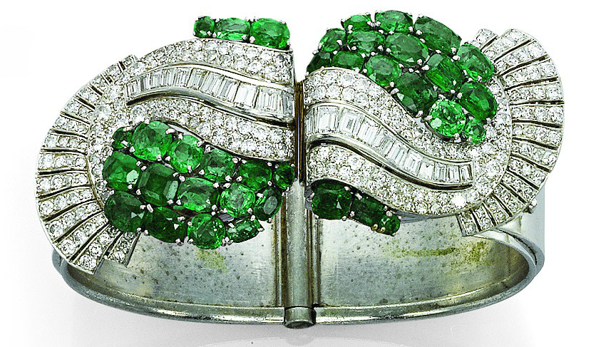 Art Deco Emerald & Diamond Bangle. Hinged bangle with two detachable clip terminals of stylized scrolling design set with various-cut emeralds & diamonds.