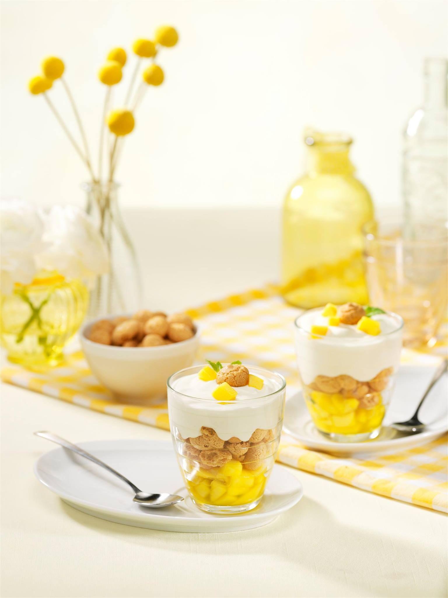 Passievrucht – mango dessert (4 Pers.) 1 mango, geschild in kleine blokjes 3 el passievruchtazijn (O&V) 5 takjes munt 250 ml slagroom 1 el suiker 5 el Griekse yoghurt 1 citroen 24 amaretti koekjes, 20 in brokjes, 4 ter garnering (O&V) of cantuccini's (O&V)  -Doe de helft van de mangoblokjes in een steelpan en giet de passievruchtazijn erbij . Voeg de blaadjes van 4 takjes munt toe, stoof enkele minuten en laat afkoelen . Voeg de overige mango-blokjes aan de gestoofde mango toe ( Hou een paar…