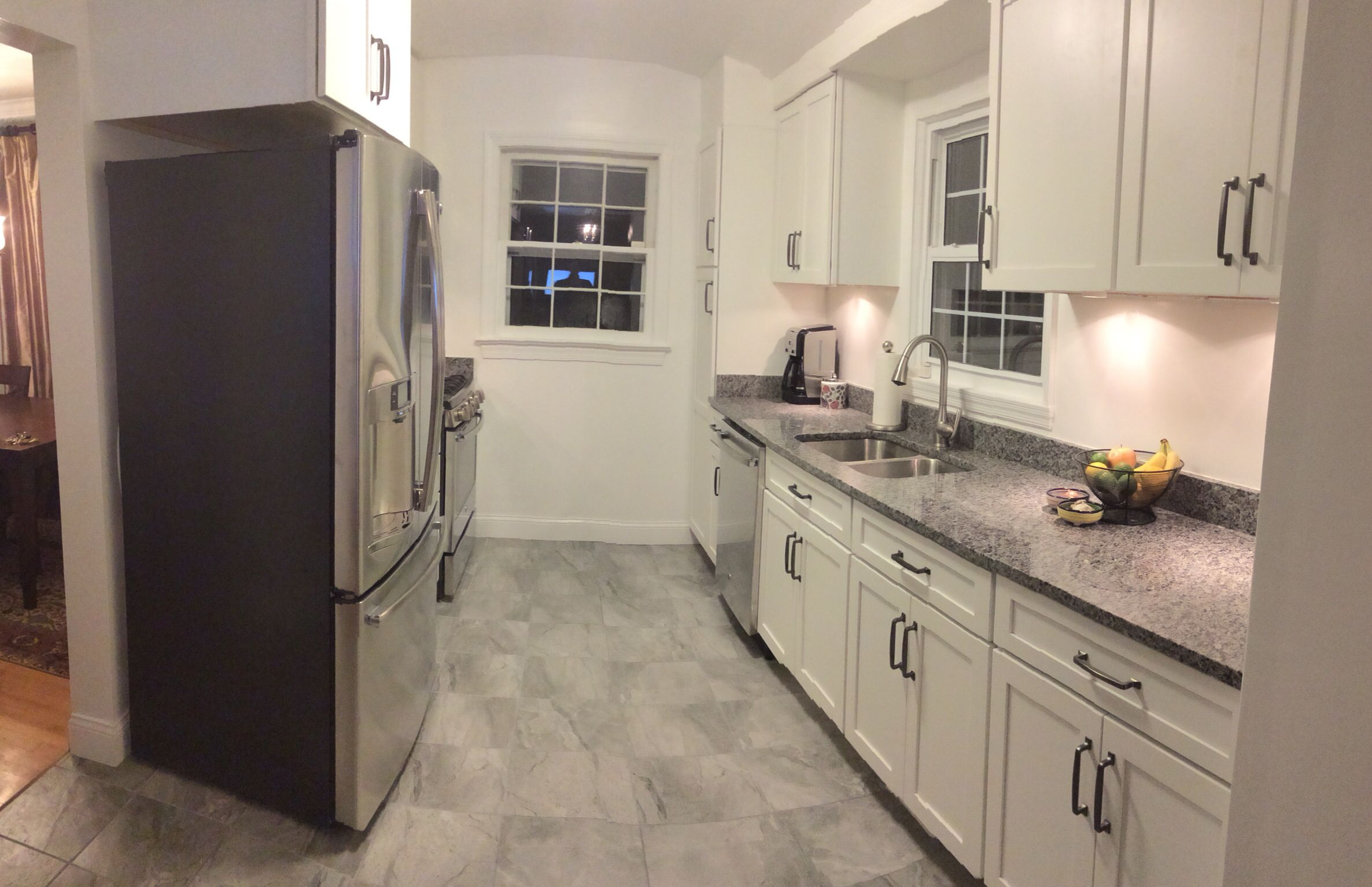 White Kitchen With Shaker Style Cabinets And Stainless Appliances New Caledonia Granite Ame Vinyl Flooring Kitchen White Kitchen Tiles White Shaker Kitchen