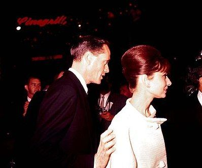 "The actress Audrey Hepburn photographed with her husband Mel Ferrer (actor, dialogue coach and film director) during their arrival at Grauman's Chinese Theatre (now known as TCL Chinese Theatre), located on Hollywood Boulevard, in Hollywood, a neighborhood in the central region of Los Angeles, California (USA), for the American premiere of ""West Side Story"", on December 13, 1961.Audrey was wearing:Cocktail ensemble: Givenchy (of silk grosgrain in a shade of cream, coat with a small sta..."