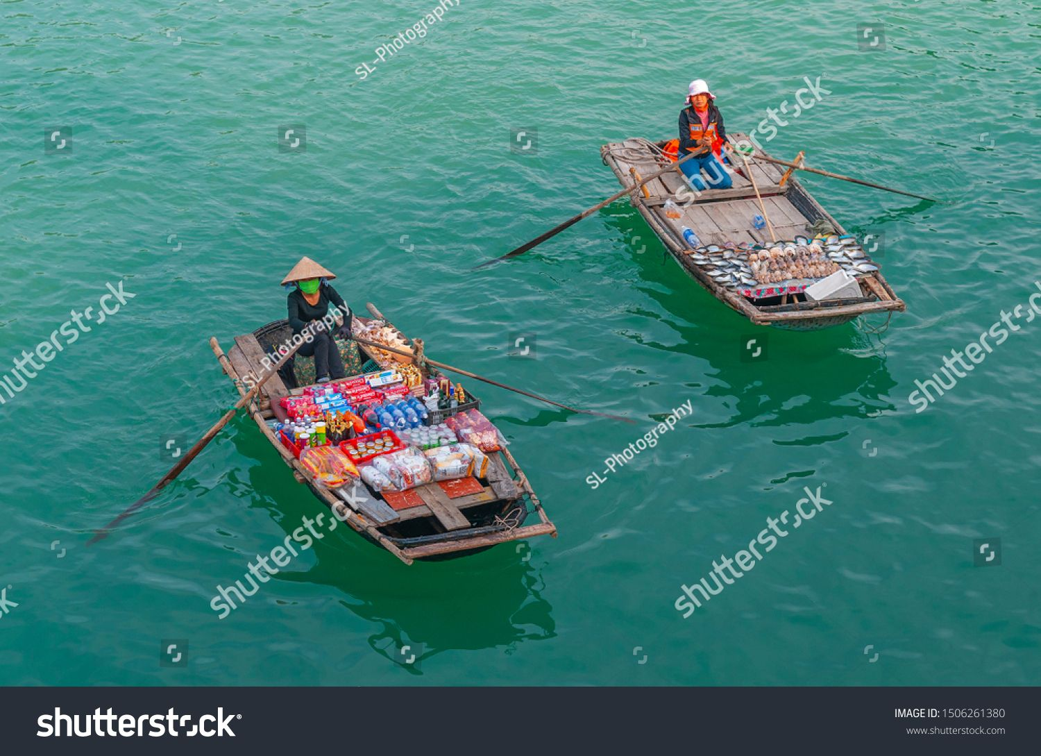 HALONG BAY, VIETNAM - NOVEMBER 23, 2009: Two local saleswomen in traditional boats selling food and drinks in the emerald waters of Halong Bay in North Vietnam. #Sponsored , #SPONSORED, #local#traditional#saleswomen#BAY