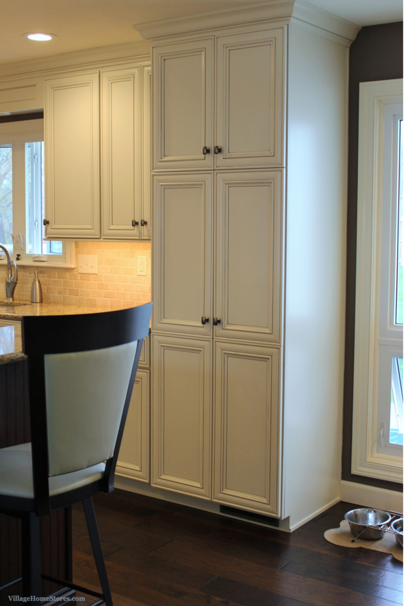 A tall pantry cabinet with slide out shelves within adds storage to this new kitchen design while capping off the end of the kitchen area