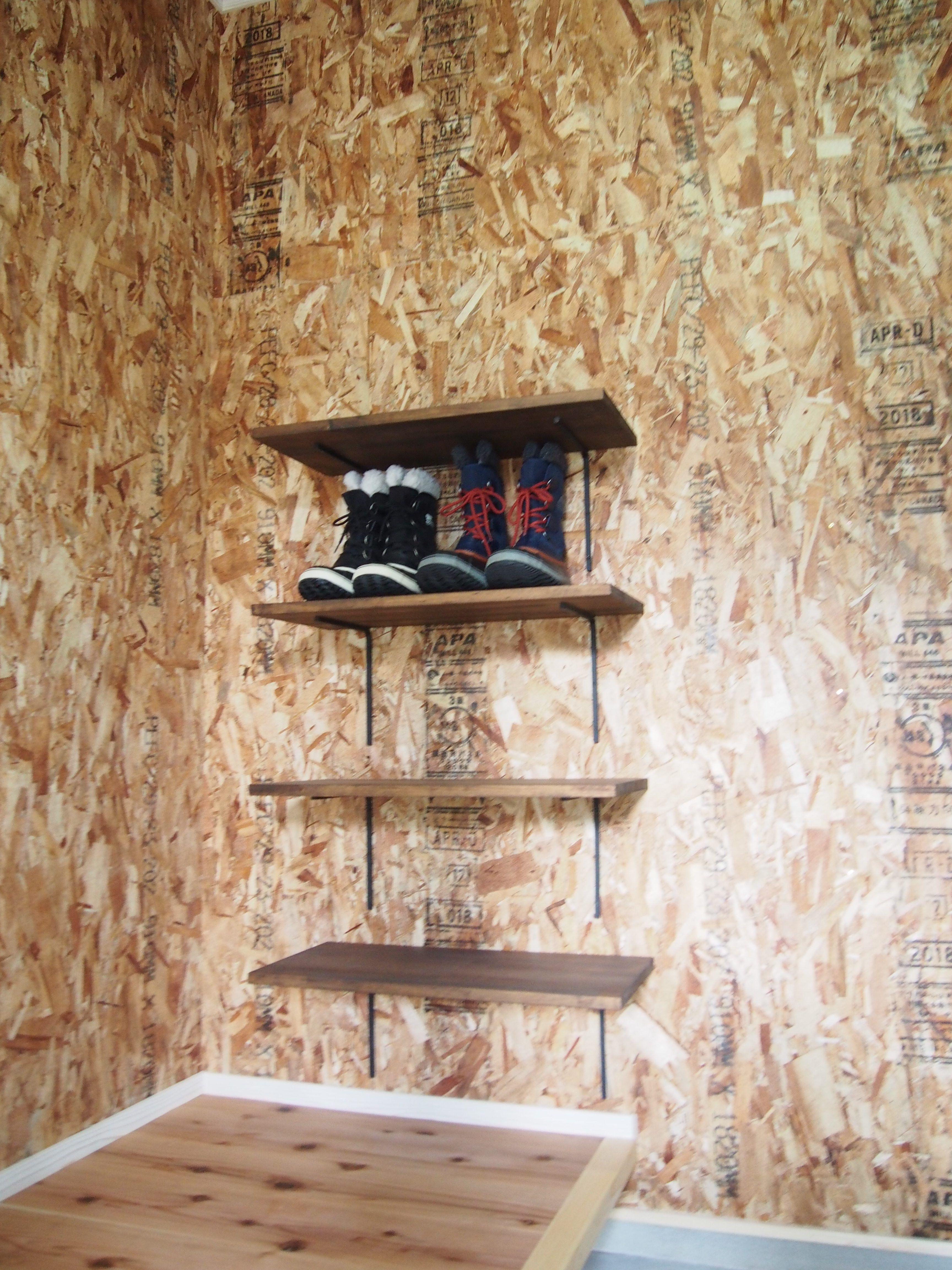 玄関に入り 正面のrの垂れ壁を抜けると そこはカッコイイ 男前な空間の土間収納 天井は板貼り茶色塗料仕上げ壁はosb