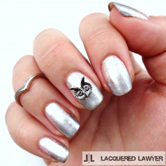 White and silver gradient nails with an owl charm.