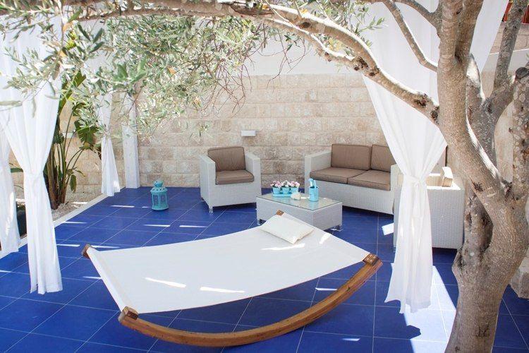 blaue Bodenfliesen auf Terrasse und weiße Vorhänge