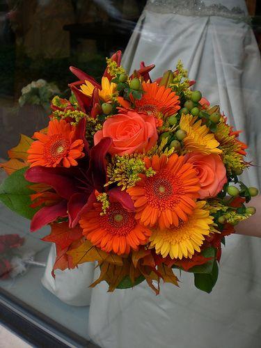 fall wedding flowers, evt oransje blomster, grønne blader og kvister i små vaser på middagsbordene og ved kakene