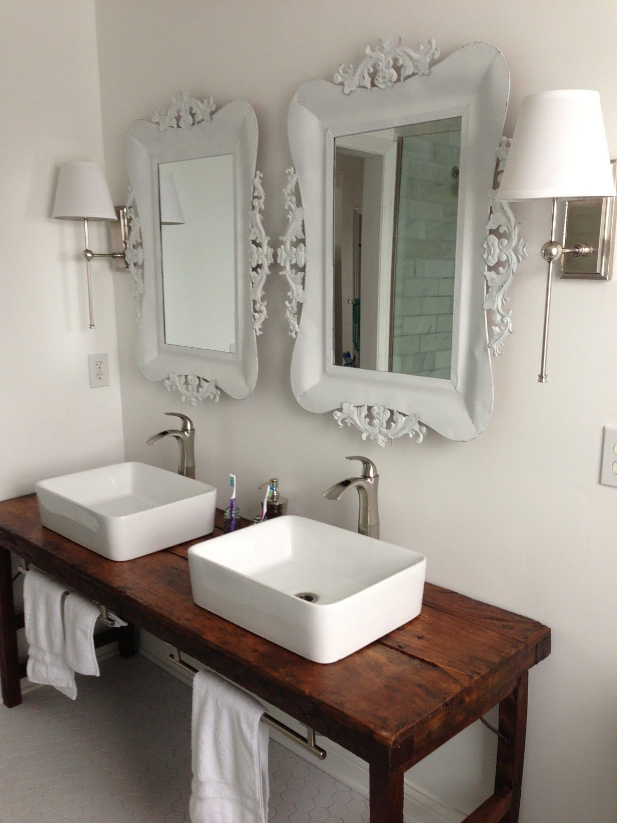 White bathroom with vessel sinks and wood table as vanity for Vessel sink bathroom ideas