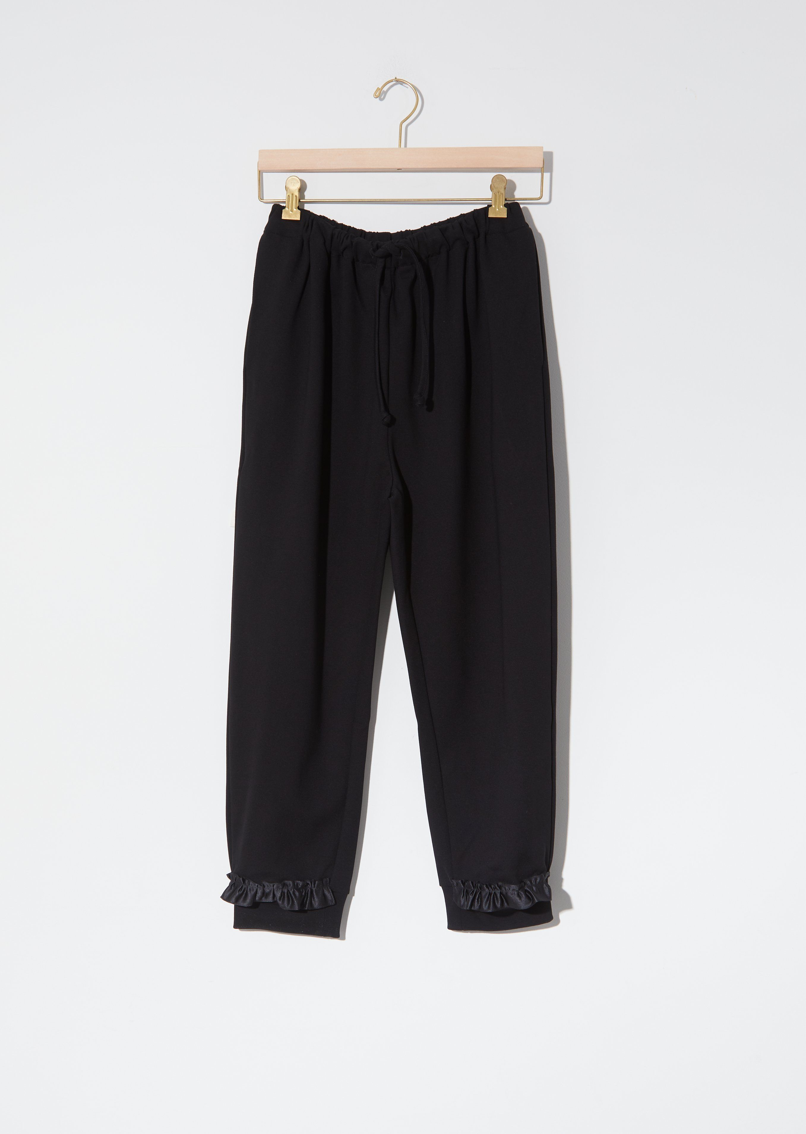 Simone Rocha Jersey Drop Bite Jogging Pants in Black. Cropped sweatpants with elasticated drawcord waistband and featuring tonal satin ruffle trim with cut-out detailing at hem. tapered silhouette, relaxed fit tonal drawcords slit detail at side seam Care: Machine Wash. Sizing: Universal (XS-L). Runs true to size, we recommend ordering your normal size. Size Extra Small measures 22.5