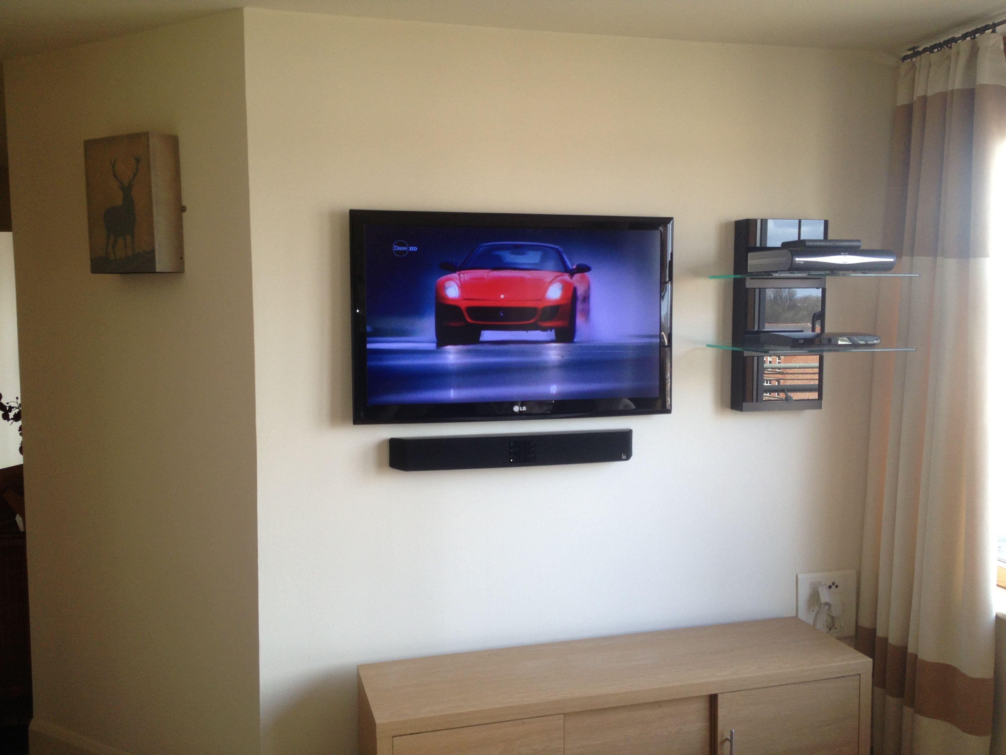 flat screen tv with soundbar and floating av shelves av installs hidden cabling experts