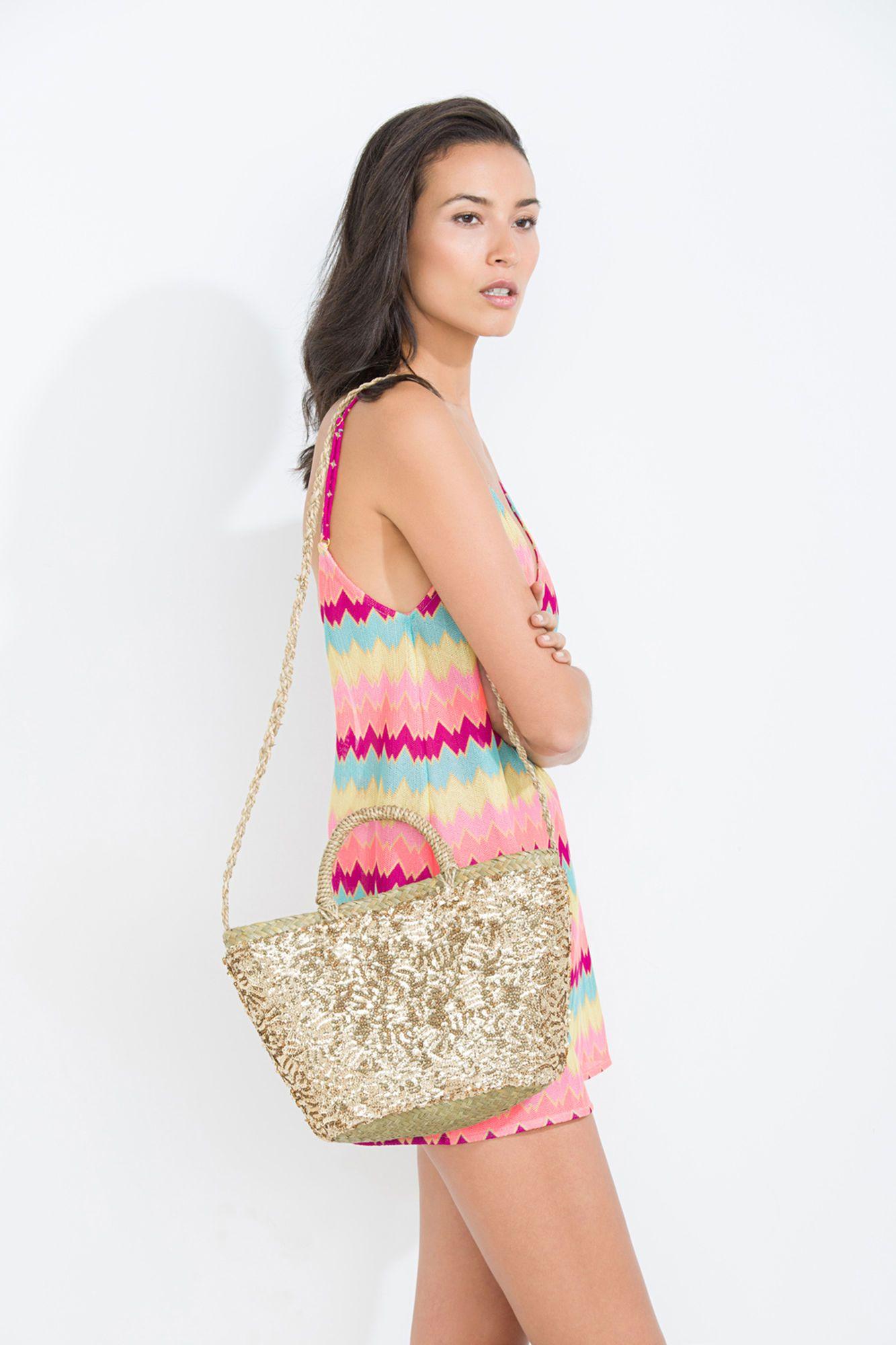 Bolso de playa, tipo cesta, hecho de paja con dos asas cortas, una asa larga para llevar la hombro y decorado del lentejuelas.