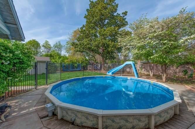 This Round Above Ground Pool Is Surrounded By A Concrete Pool Area And Adorned With A Slid Above Ground Pool Slide Backyard Pool Landscaping Above Ground Pool