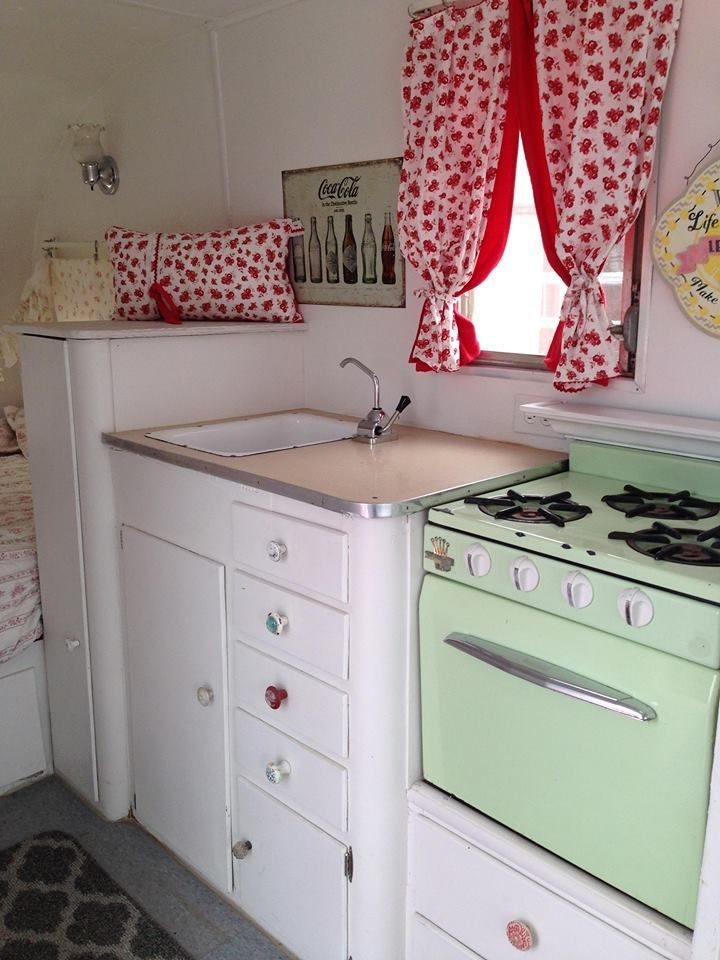Not sure if the light fixture is original, but it sure is pretty. I love the pink counter with the mint green stove. I wouldn't use red, but that's just me. Nope, I would use a ton of pink, bunches of roses, and yards of fabric, a chandelier and shabby it up!